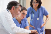 Doctor and two nurses looking at laptop — Stock Photo