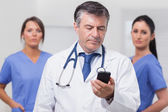 Doctor looking at phone with his team of nurses — Stock Photo