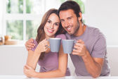 Couple looking at the camera with a coffee — Foto de Stock