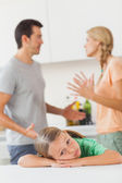 Couple arguing behind a sad girl — Stockfoto