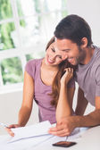 Smiling lovers in front of invoices — Stock Photo