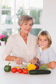 Granny cutting vegetables with her grandson — Stock Photo