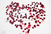 Pink confetti scattered in heart shape over valentines day — Stock Photo