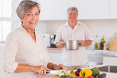 Old couple smiling preparing food — Stock Photo