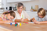 Granny and her grandchildren drawing seriously — Stock Photo