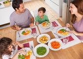 Familia sonriendo alrededor de una comida sana — Foto de Stock