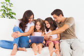 Smiling family using a digital tablet — Stock Photo