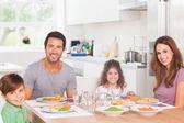 Famille souriante en train de dîner — Photo