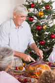 Grandfather carving turkey at christmas — Stock Photo