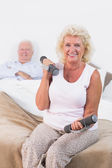 Old woman lifting weights — Stock Photo