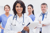 Female doctor with clipboard and her team smiling — Stock Photo