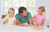 Father and his children cutting cookies out — Stock Photo