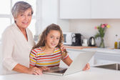 Grandmother and little girl looking at the camera with laptop — Stock Photo