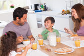 Family laughing around breakfast — Stok fotoğraf