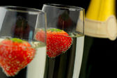 Strawberries floating in two champagne flutes — Stock Photo