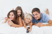 Family lying on the bed with a remote — Stok fotoğraf