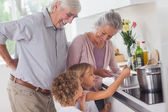 Children cooking with grandparents — Stock Photo