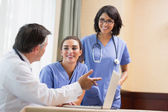 Doctor showing smiling nurses something on laptop — Stock Photo