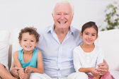 Grandfather and children sitting on the sofa — Stock Photo