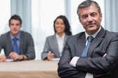 Businessman with arms crossed sitting with business panel — Stock Photo