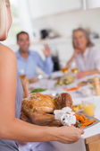 Woman bringing the turkey to the dinner table — Stock Photo