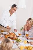 Father carving the turkey at the head of the table — Stock Photo
