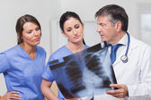 Doctor speaking about x-ray with nurses — Stock Photo