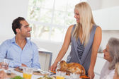 Happy wife bringing turkey to the table — Stock Photo
