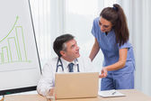 Doctor and nurse discussing something on the laptop — Stock Photo