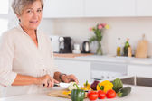 Elderly woman cutting vegetables on a cutting board with a smile — Stock Photo
