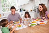 Familie lachen um eine gute mahlzeit — Stockfoto