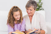Portrait of a child and her grandmother reading a book — Stock Photo