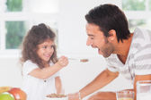 Little girl feeding cereal to father — Stock Photo