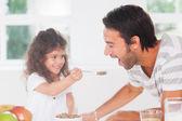 Menina alimentação cereais ao pai — Foto Stock