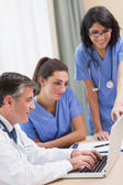 Nurses and doctor looking at laptop — Stock Photo