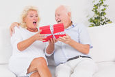 Surprising old woman receiving a gift — Stock Photo