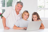 Grandfather and children looking at the camera with laptop in fr — Stock Photo