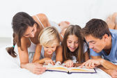 Family reading a book on the bed — Stock Photo
