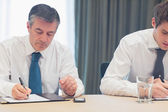 Businessmen taking notes — Stock Photo