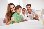 Kijken naar de camera met een laptop en gelukkige familie — Stockfoto