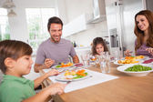 Family smiling around a good meal — Stock Photo