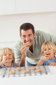 Father and his sons eating cookies — Stock Photo
