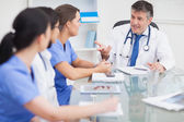 Meeting between a doctor and three nurses and a doctor smiling — Stock Photo