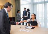 Woman handing name tag to businessman — Stock Photo