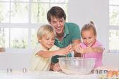 Children breaking eggs into a bowl — Stock Photo