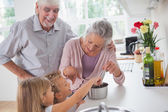 Smiling grandparents helping children to cook — Stock Photo