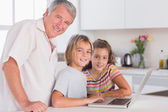 Grandfather and children looking at the camera together with lap — Foto Stock