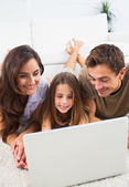 Family lying on a carpet with the laptop — Stock Photo