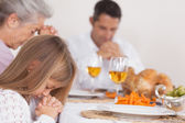 Little girl saying grace with family — Stock Photo