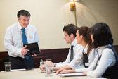 Toplantıda tablet kullanarak iş adamı — Stok fotoğraf